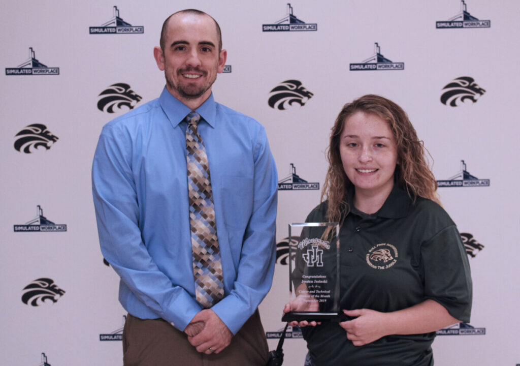 Engineering teacher Gavin Hartle and Jessica Jasinski pose for a picture while Jessica holds her Student of the Month plaque.