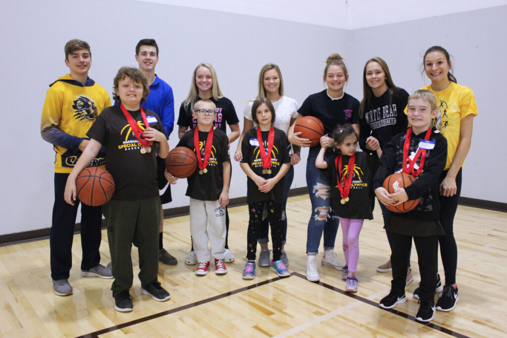 Several Special Olympians proudly display the medals they won. Their peer tutors are grinning from ear to ear because of the athletes' accomplishments.