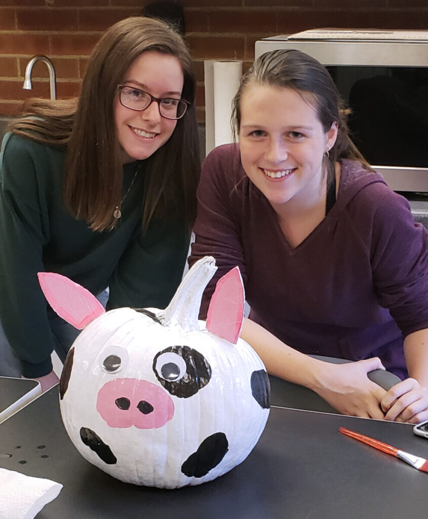 "Pictured from left: The winners Ashley Schwing and Abby Elliott are shown with their pumpkin, ""Ed the Cow."""