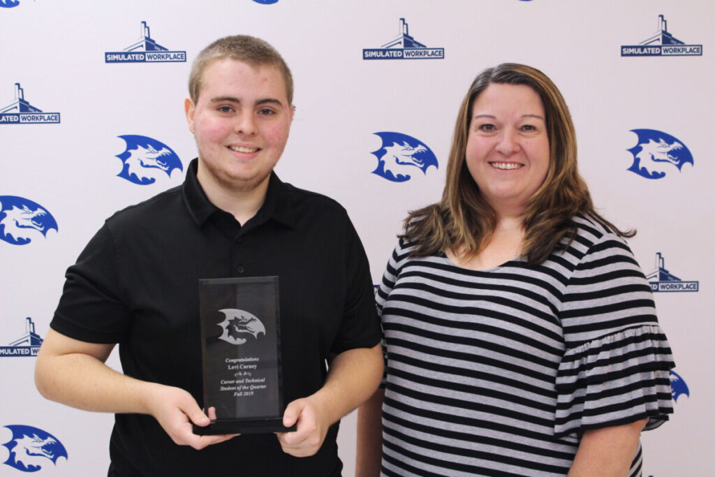 Business teacher Rhonda Williams presents Levi Carney with his CTE Student of the Quarter plaque.