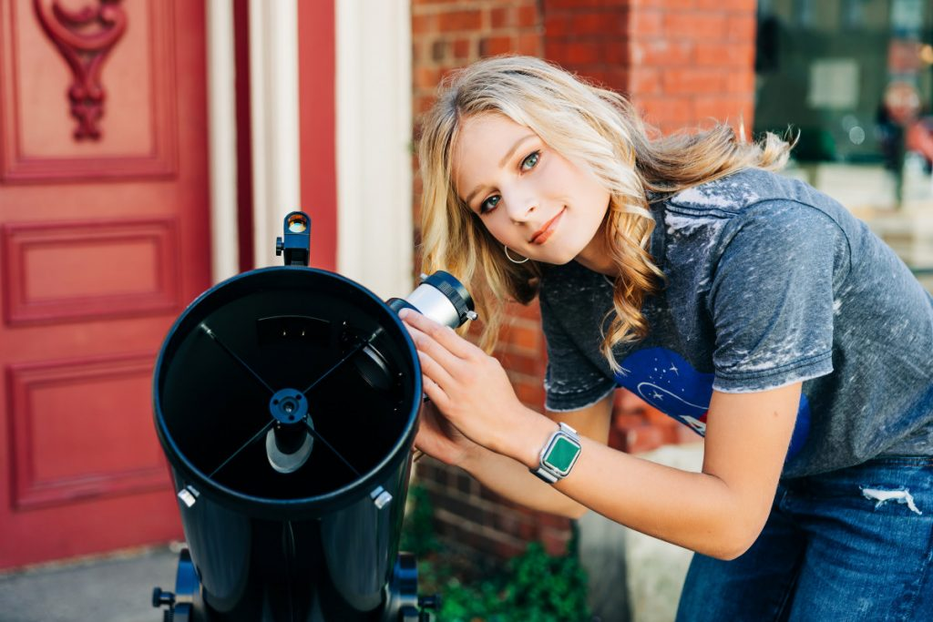 Zara is wearing a grey NASA shirt and is looking into a telescope in front of a red brick building.