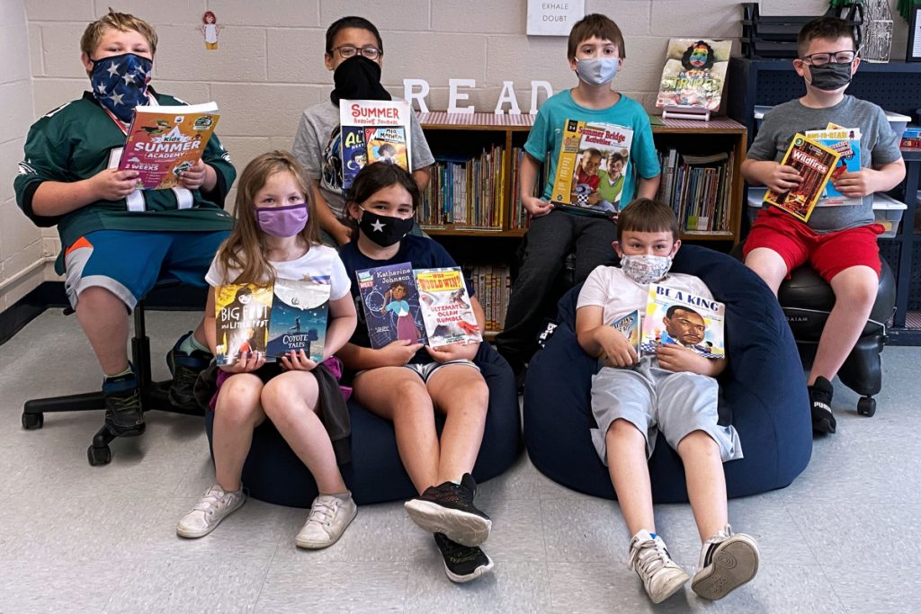 Central Elementary students are excited get new books to read during summer break. Pictured from left front row: Nevaeh Plants, Erika Gibson and Boston Gilpin. Back row from left: Levi Johnson, Tristan Ross, Randall Brock and Kayden Roseberry. They are sitting in beanbag chairs.
