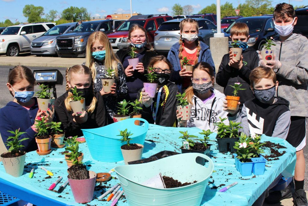 Several members of the Hilltop Elementary Schools Kindness Crew show off the flowerpots they painted and filled with plants.