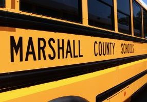 side view of a yellow school bus with Marshall County Schools written in black on the side with black stripes.