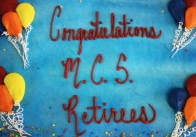 Cake with blue icing and blue, red, yellow and orange icing balloons. Congratulations MCS Retirees is written in cursive in red.